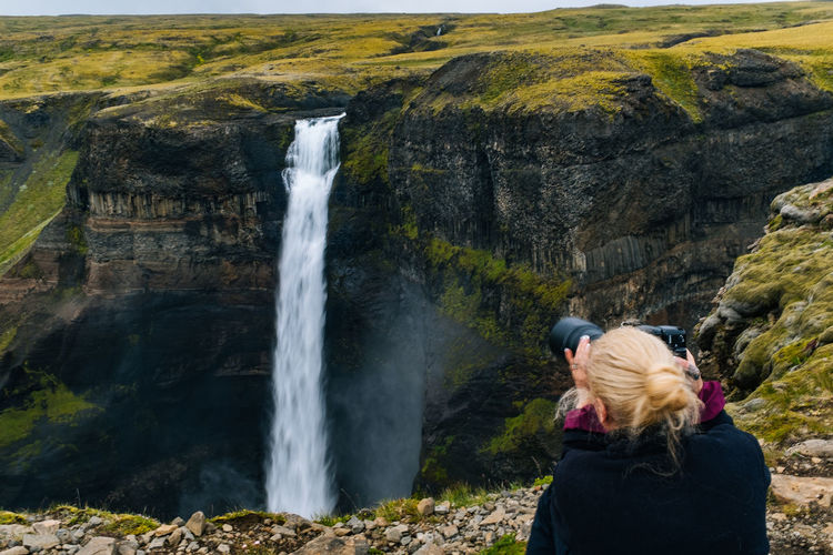 Beauty In Nature Camera - Photographic Equipment Cliff Day Iceland Leisure Activity Lifestyles Long Exposure Motion Nature One Person Outdoors People Photographing Power In Nature Real People Rock - Object Rock Formation Scenics Sky Standing Water Waterfall Women