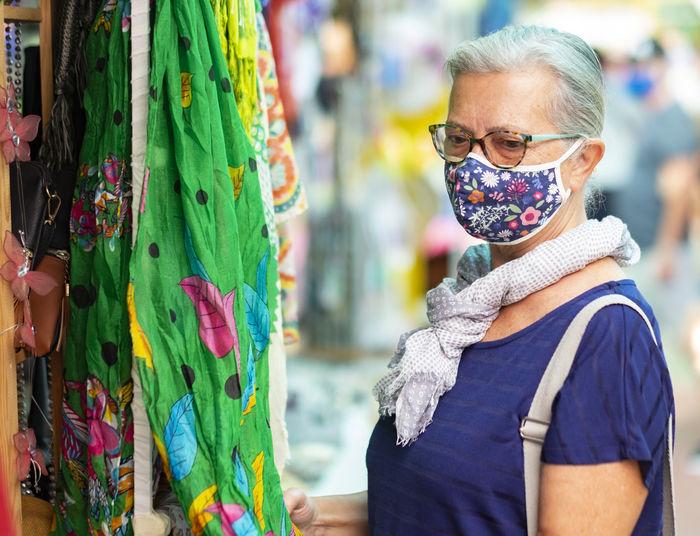 Senior woman wearing mask standing at market