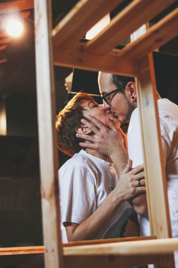 Couple kissing while standing by rack