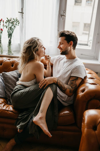 Affectionate couple sitting on sofa at home