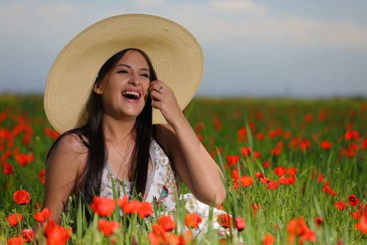 Portrait of young woman with red poppy flowers in field