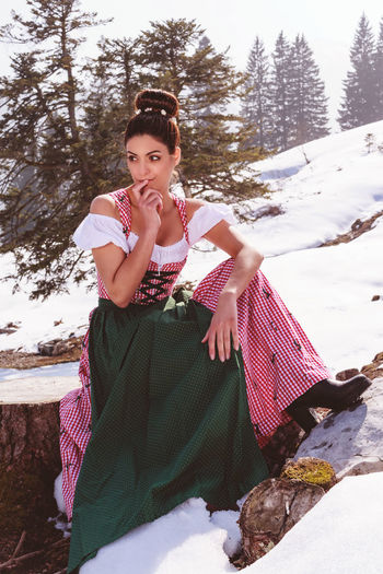 Woman in the Dirndl Dress in the great outdoors in Alpine, with a thoughtful expression Bavaria Nature Cold Temperature Day Dirndl Front View Full Length Hairstyle Happiness Leisure Activity Lifestyles Looking At Camera One Person Outdoors Portrait Real People Smiling Snow Thought-provoking Tree Warm Clothing Winter Women Young Adult Young Women