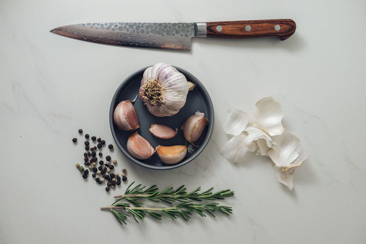 Garlic, rosemary, peppercorns and a knife on white marble.