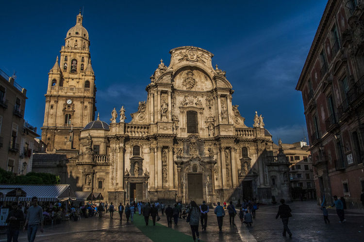 People at murcia cathedral against sky