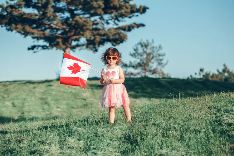 Girl holding canadian flag while standing on grass against sky