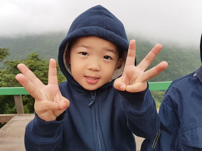 Portrait of cute boy wearing warm clothing while gesturing against mountain