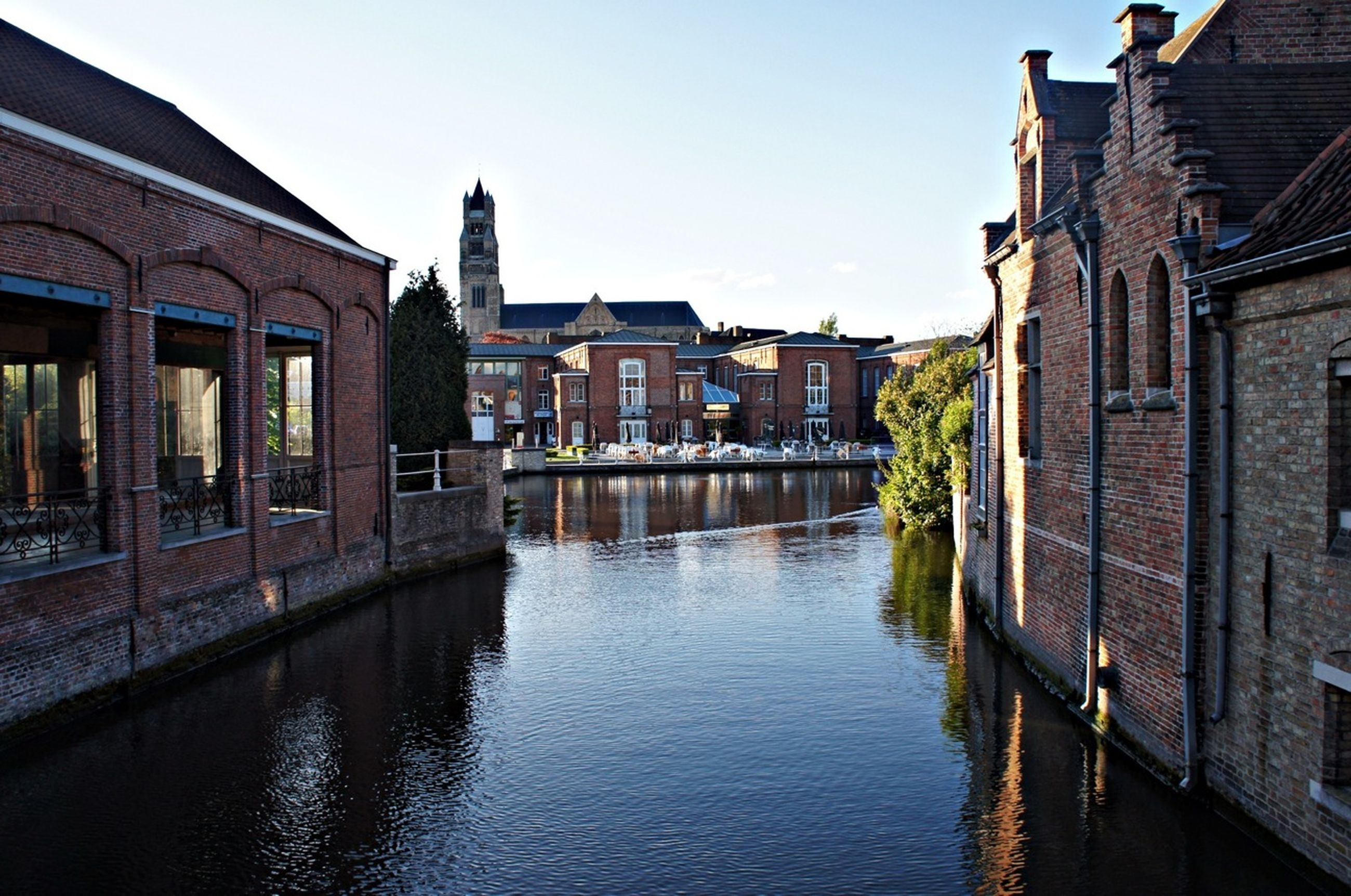architecture, building exterior, built structure, water, waterfront, canal, reflection, residential structure, clear sky, residential building, house, building, river, city, sky, rippled, outdoors, day, no people, window