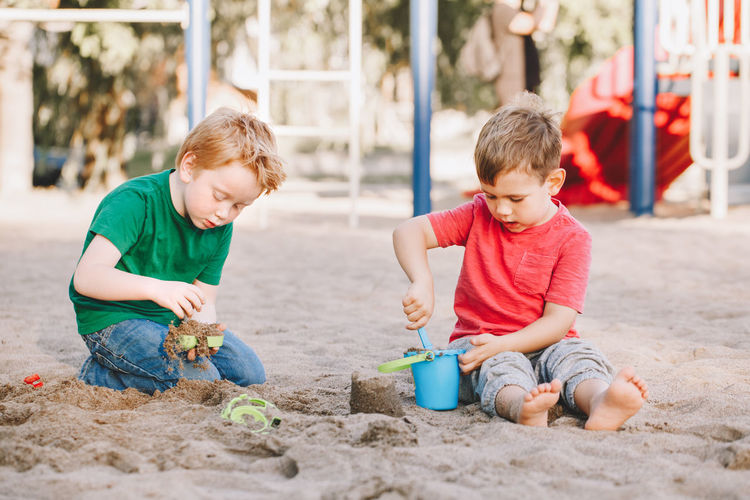 Boys playing with sand at beach