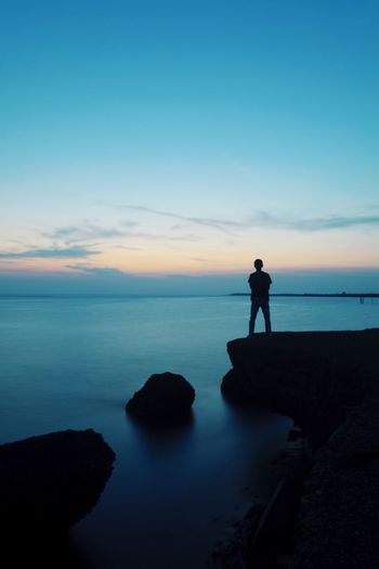 Adventure Cliff Copy Space Backgrounds Sunlight Freshness Blue Hour Man Outdoors Sunset Silhouette Sea Full Length Water Sunset Silhouette Beach Standing Discovery Adventure Photography Themes Seascape Coast Hiker Calm Coastline Tide Coastal Feature Ocean Horizon Over Water