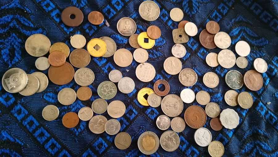 Directly Above Shot Of Various Coins On Textile