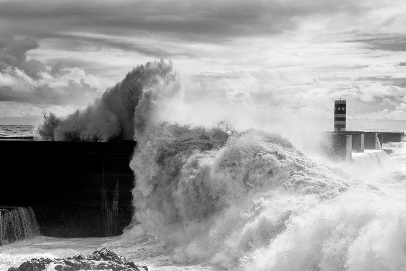 Sea Waves Splashing On Groyne Against Sky