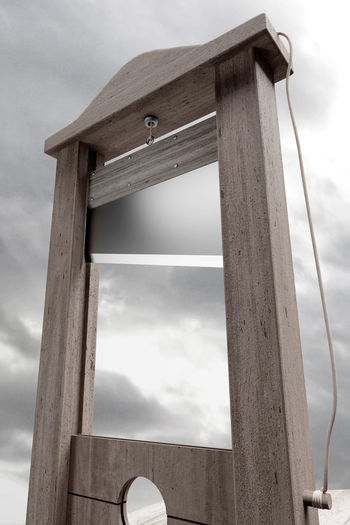 Low Angle View Of Guillotine Against Cloudy Sky