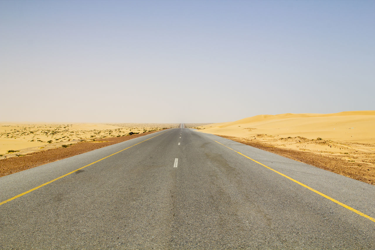 road, sky, transportation, direction, symbol, road marking, sign, marking, desert, the way forward, landscape, clear sky, diminishing perspective, vanishing point, scenics - nature, nature, environment, tranquil scene, copy space, no people, arid climate, climate, outdoors, dividing line
