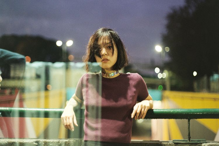 Portrait of young woman standing against railing