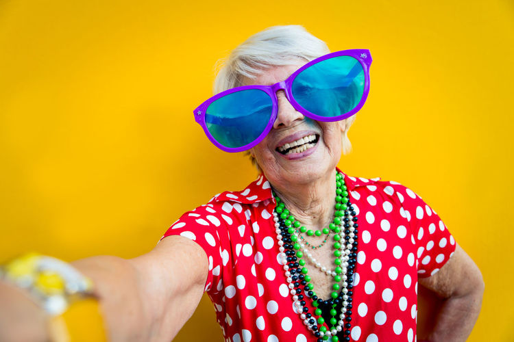 Portrait of cheerful young woman wearing sunglasses against yellow background