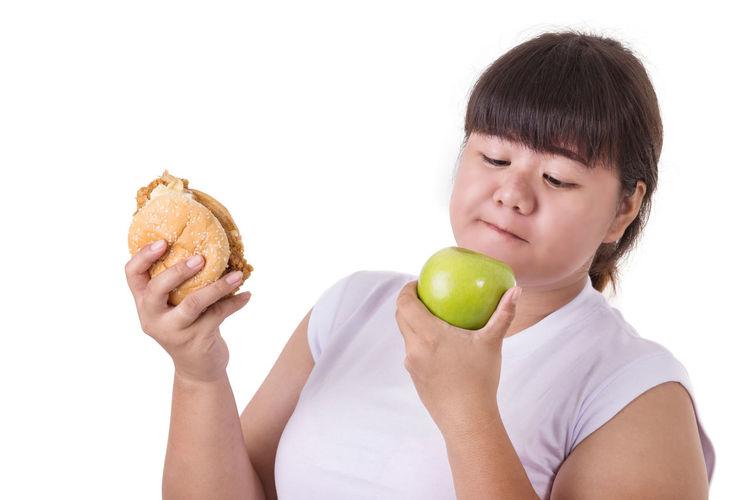 Portrait of boy holding apple against white background