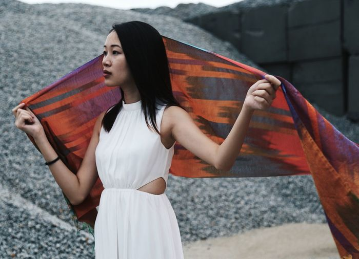Young Woman Holding Scarf Against Heap Of Gravels