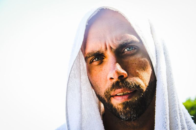 Close up portrait of bearded man wearing hood against clear sky on sunny day