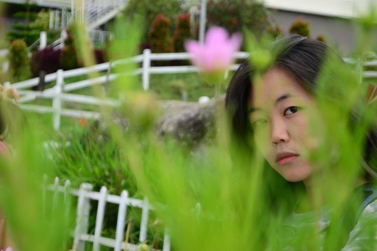 Portrait of young woman looking at plants