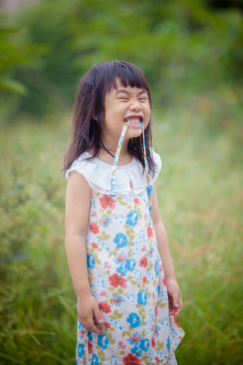 Girl with eyes closed standing on grass