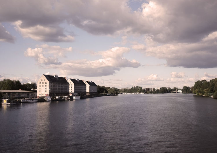 River in city against cloudy sky