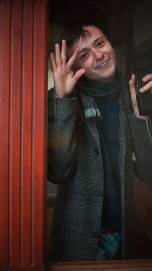 Portrait of young man seen through telephone booth
