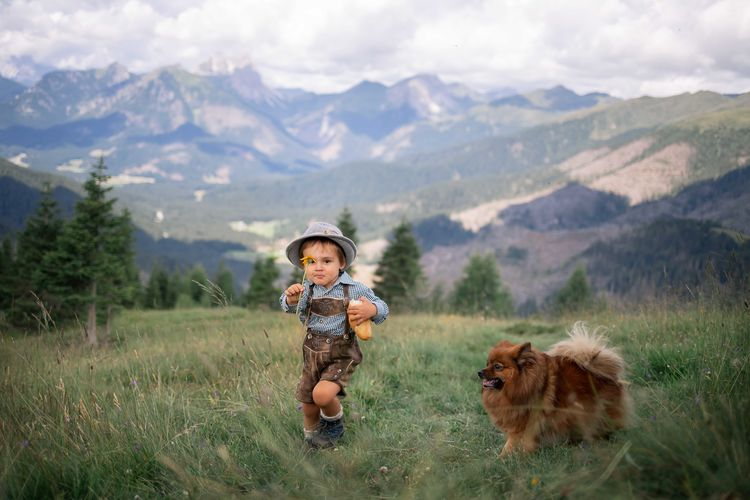 Portrait of boy holding food and flower by dog on mountain