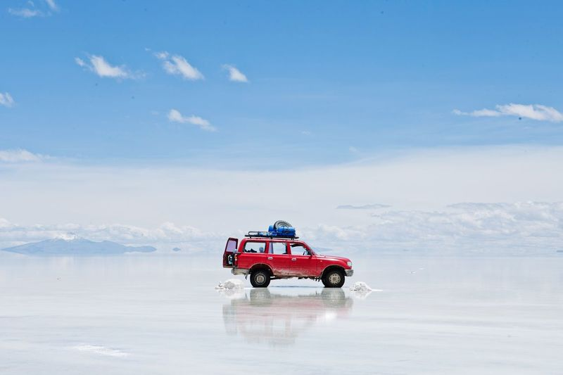 SCENIC VIEW OF Car On Wet Sand Travelling Through Bolivia