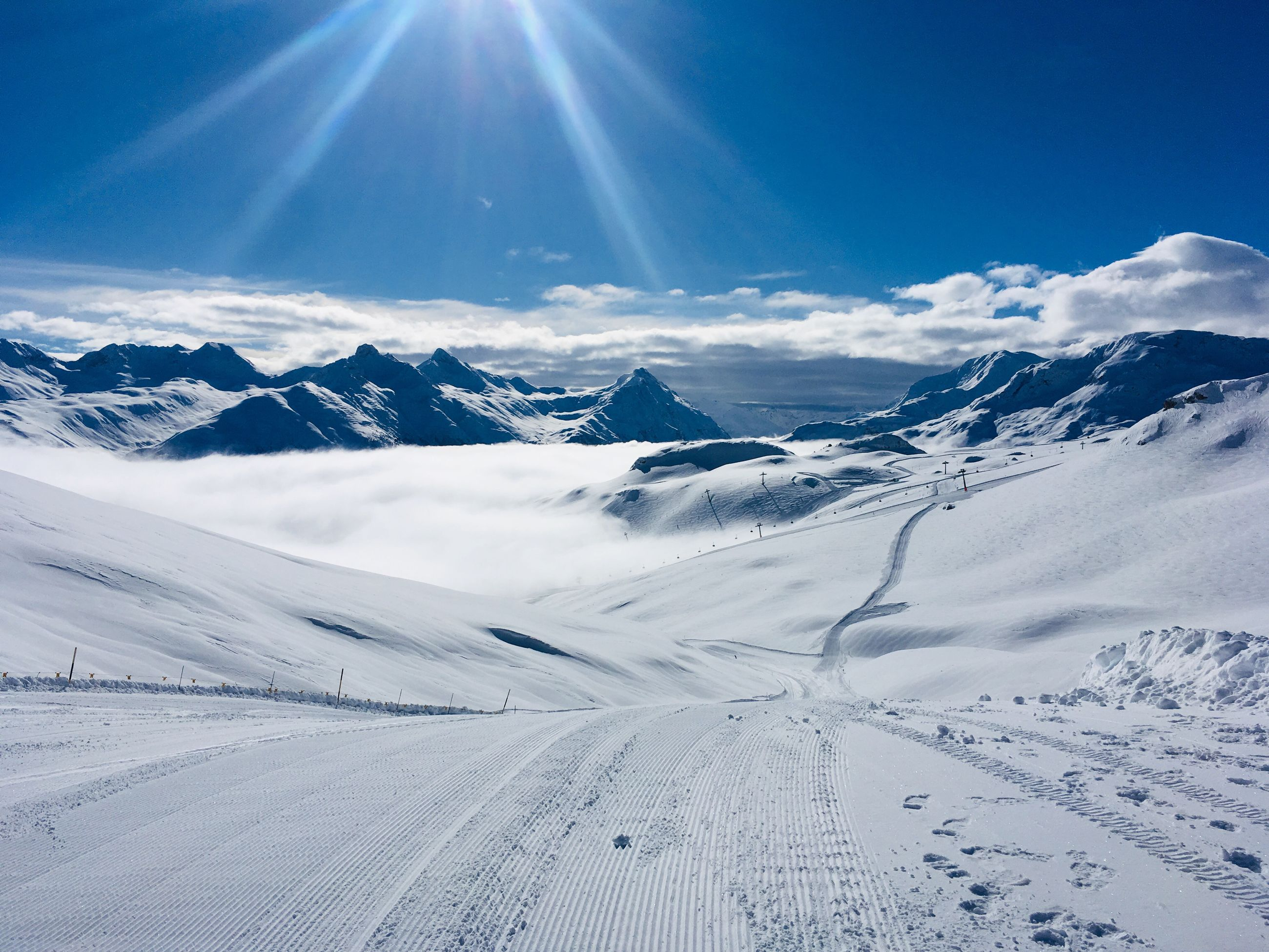 sky, snow, cold temperature, beauty in nature, winter, scenics - nature, tranquil scene, sunlight, tranquility, sunbeam, mountain, covering, environment, white color, day, landscape, ski track, cloud - sky, nature, mountain range, snowcapped mountain, lens flare, no people, sun, outdoors, bright, powder snow