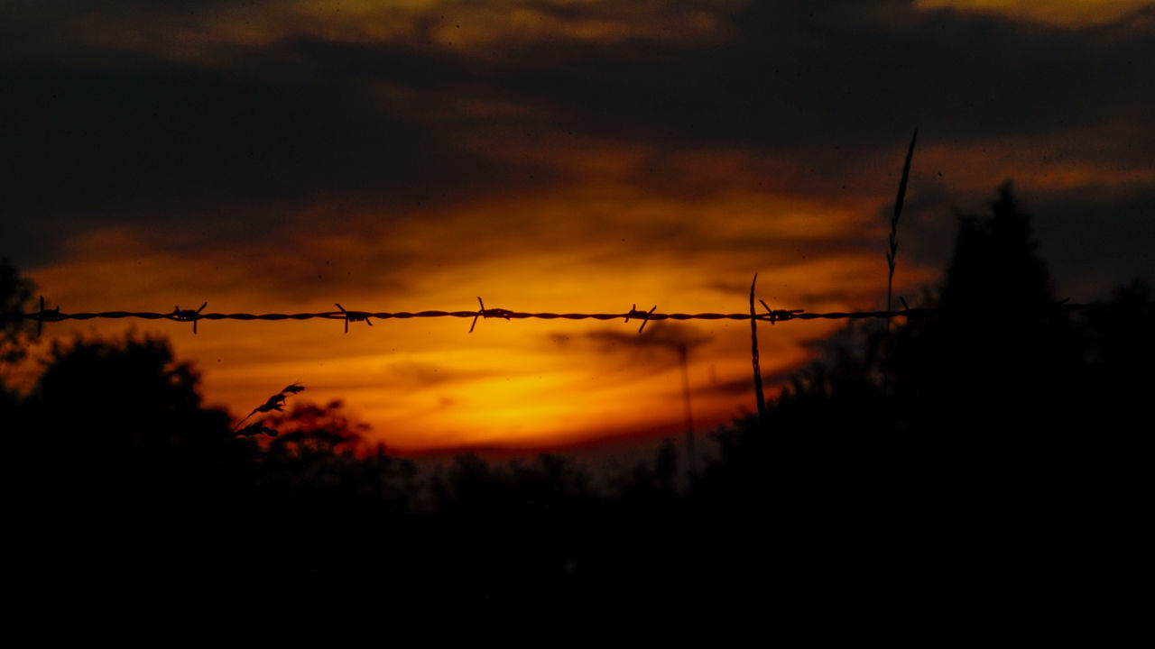 SILHOUETTE OF BARBED WIRE AGAINST SKY AT SUNSET