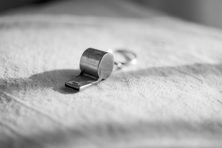 close-up of whistle on table Close-up Communication Day Equipment Februar Indoors  Man Made Man Made Object Metal No People Pattern Personal Accessory Safety Security Selective Focus Single Object Still Life Surface Level Table Textile Textured