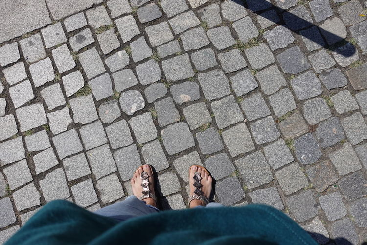 Low section of woman standing on cobblestone street