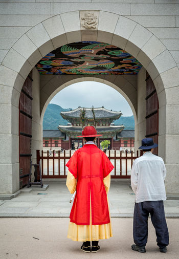 Rear view of people in traditional clothing standing at gwanghwamun