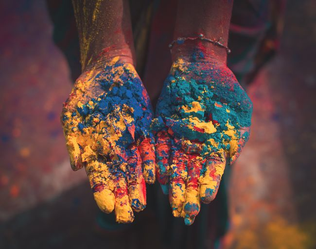 Close-up of human hand against multi colored background