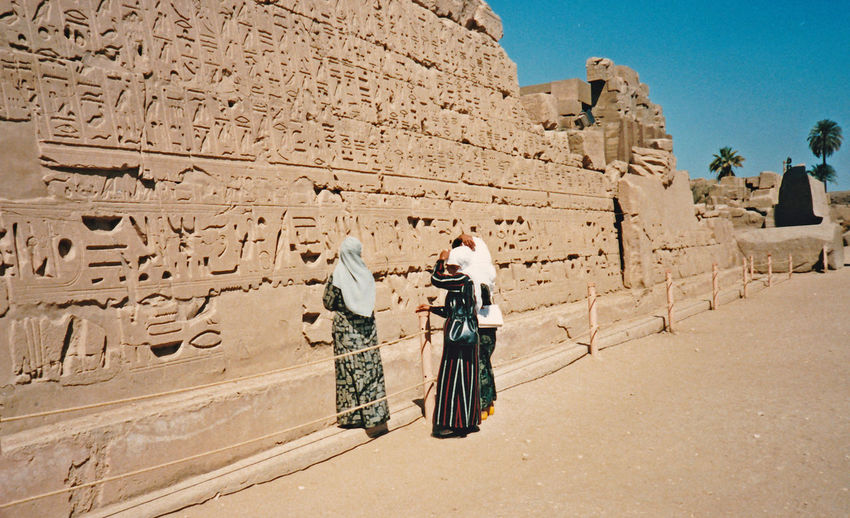 A female Arab egyptogolist (next to wall) translating the hieroglyphics to two female student that are not permitted to get any closer - Great Temple of Amun, Karnak, Luxor, Architecture People Men Sky Spirituality Travel Sunlight Day History Outdoors Ancient The Past Archaeology Adult Karnak Temple Full Length Egyptology One Person Travel Destinations Ancient Civilization Built Structure Old Ruin Luxor, Egypt Wall Carvings King - Royal Person Temple Of Amun Karnak Egyptian Student Women