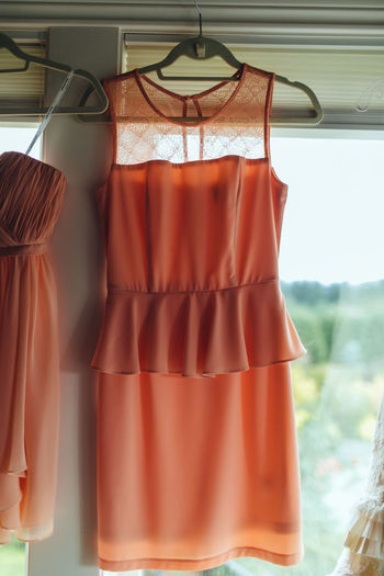 Dress hanging on window at home