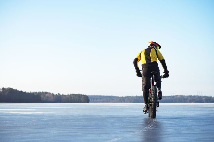 Man riding bicycle on snow against sky