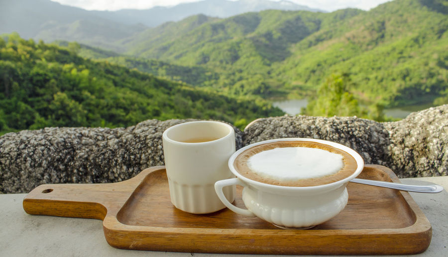 Coffee cup on table against mountains
