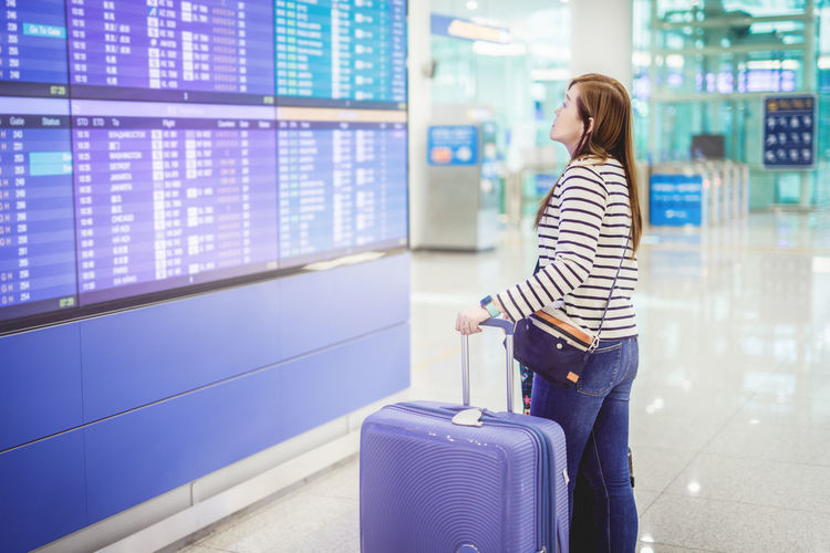 Side view of woman with luggage standing at airport