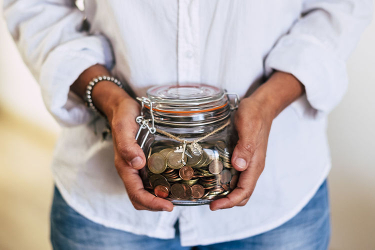 Close up of woman hands at home taking a transparent glass vase full of coins and airplane outside - economy and money for the next travel vacation - familiar business concept Midsection One Person Savings Holding Front View Finance Jar Adult Coin Business Wealth Indoors  Investment Container Hand Close-up Currency Human Hand Men Hands Cupped Responsibility Transparent Economy One Woman Only People Caucasian Casual Clothing Money Euros Dream Hoping  Reach Family