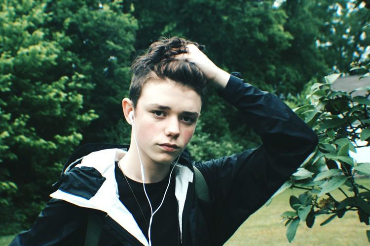 Portrait Of Boy With Hand In Hair Against Trees