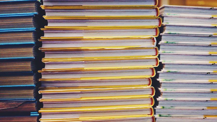 Full frame shot of books stacked indoors