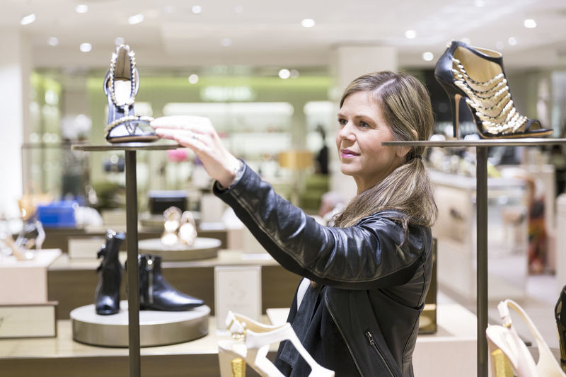 Side view of a young woman holding camera at store