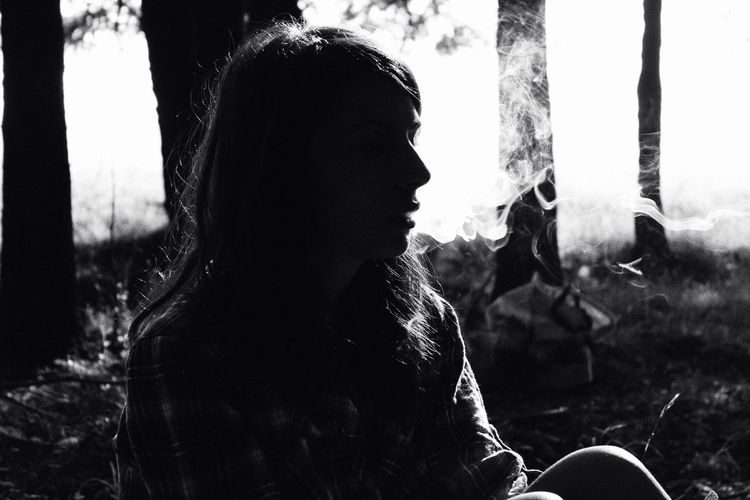 Woman smoking cigarette while sitting against trees