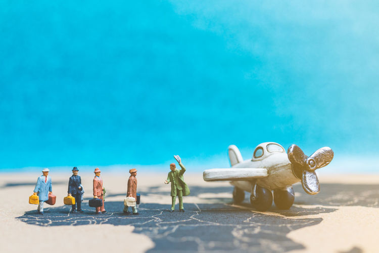 Close-up of toys on beach against blue sky