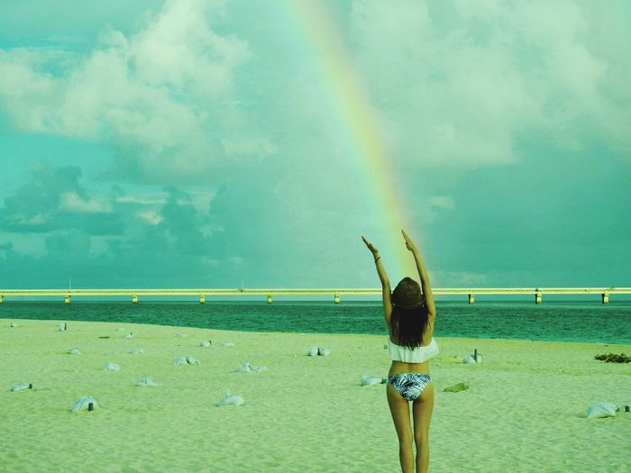 Rear view of woman standing against rainbow at beach