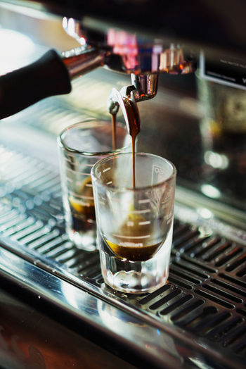 Close-up of espresso maker pouring coffee in glass