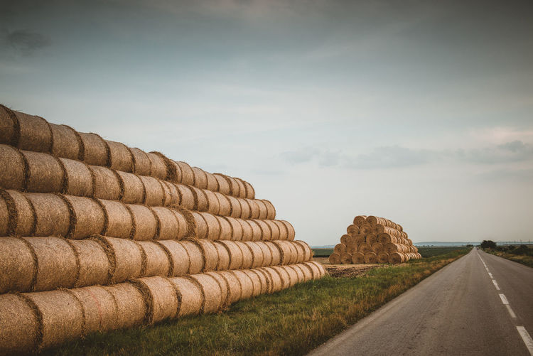 Stack of road by agricultural field against sky