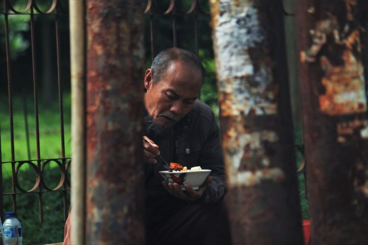 Side view of man eating food outdoors