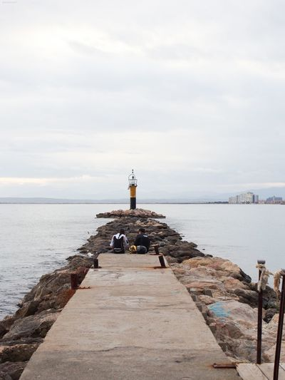 Lighthouse on pier by sea against sky